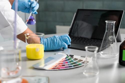 Labor, Tigel, Farbtafel, gelbe Füssigkeit, Laptop, Hände, Chemikalien